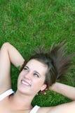 Frau, die auf dem Gras, lächelnd liegt Lizenzfreie Stockfotos