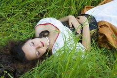 Frau, die auf dem Gras liegt Lizenzfreie Stockbilder