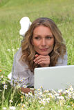 Frau, die auf dem Gras liegt Lizenzfreie Stockfotografie