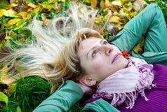Frau, die auf dem Gras mit Beere im Mund liegt Stockfotografie