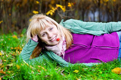 Frau, die auf dem Gras mit Beere im Mund liegt Lizenzfreie Stockfotografie