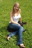 Frau, die auf dem Gras sitzt Lizenzfreie Stockfotografie