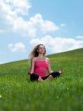 Frau, die auf dem Gras sitzt Lizenzfreie Stockfotos