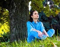 Frau, die auf dem Gras sitzt Stockbild