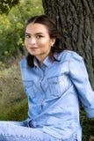 Frau, die auf dem Gras sitzt Stockbilder