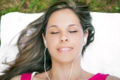 Frau, die auf dem Gras während hörende Musik sich entspannt Stockfoto