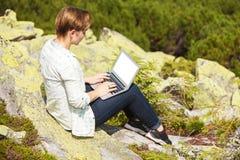 Frau, die auf dem Hügel mit Laptop sitzt Stockfotos