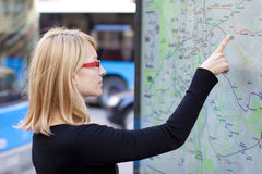 Frau, die auf dem Metrokartenvorstand schaut Stockbild
