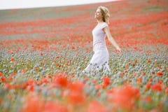 Frau, die auf dem Mohnblumegebiet geht Lizenzfreie Stockbilder