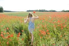 Frau, die auf dem Mohnblumegebiet geht Stockfotos