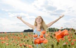 Frau, die auf dem Mohnblumegebiet zujubelt Stockfotografie
