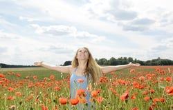 Frau, die auf dem Mohnblumegebiet zujubelt Lizenzfreies Stockfoto