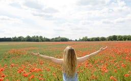 Frau, die auf dem Mohnblumegebiet zujubelt Stockbild