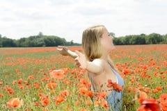 Frau, die auf dem Mohnblumegebiet zujubelt Stockfoto