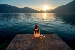 Frau, die auf dem Pier bei Sonnenaufgang sitzt Stockfotografie