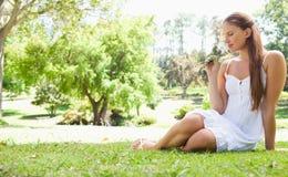 Frau, die auf dem Rasen beim Riechen einer Blume sitzt Stockbilder