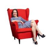 Frau, die auf dem roten Stuhl stillsteht Lizenzfreies Stockfoto