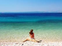 Frau, die auf dem schönen Strand sitzt Lizenzfreies Stockfoto