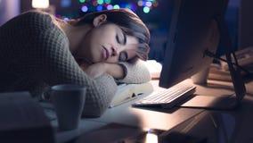 Frau, die auf dem Schreibtisch nachts schläft lizenzfreies stockbild