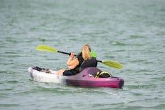 Frau, die auf dem See Kayak fährt lizenzfreie stockbilder