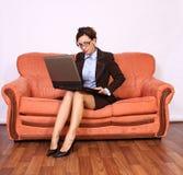Frau, die auf dem Sofa arbeitet an Schossoberseite sitzt stockfoto