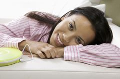 Frau, die auf dem Sofa hört Musik liegt Lizenzfreies Stockfoto