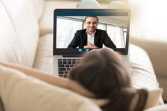 Frau, die auf dem Sofa plaudert mit Freund über Videoanruf liegt lizenzfreie stockbilder