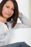 Frau, die auf dem Sofa sich entspannt Lizenzfreie Stockfotografie