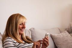 Frau, die auf dem Sofa simst Stockfotos