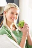 Frau, die auf dem Sofa zu Hause isst Apple sich entspannt Lizenzfreie Stockbilder