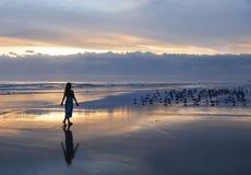 Frau, die auf dem Strand bei Sonnenaufgang sich entspannt Stockfotos