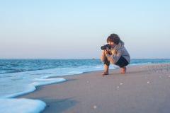 Frau, die auf dem Strand, bereitend, vor ein Foto zu machen sitzt Lizenzfreie Stockfotografie