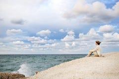 Frau, die auf dem Strand betrachtet das Meer und den Himmel sitzt Lizenzfreie Stockfotografie