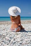 Frau, die auf dem Strand ein Sonnenbad nimmt lizenzfreie stockfotos