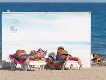 Frau, die auf dem Strand ein Sonnenbad nimmt stockfotos