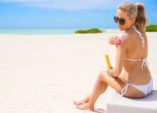 Frau, die auf dem Strand ein Sonnenbad nimmt und Sonnenschutzcreme aufträgt Lizenzfreie Stockfotos