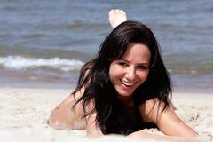 Frau, die auf dem Strand liegt Stockbild