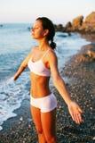 Frau, die auf dem Strand meditiert lizenzfreie stockbilder