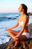 Frau, die auf dem Strand meditiert. Stockfoto