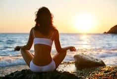 Frau, die auf dem Strand meditiert Stockfoto