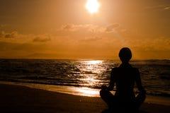 Frau, die auf dem Strand meditiert Stockfotografie