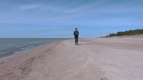 Frau, die auf dem Strand nahe Meer läuft stock video