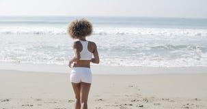 Frau, die auf dem Strand rüttelt