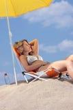 Frau, die auf dem Strand sich entspannt Stockbild