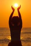 Frau, die auf dem Strand, Sonne in den Händen anhalten steht Stockfotos
