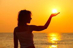 Frau, die auf dem Strand, Sonne in der Hand anhalten steht Stockfotos