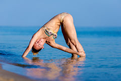 Frau, die auf dem Strand tut Yoga steht Lizenzfreie Stockfotografie