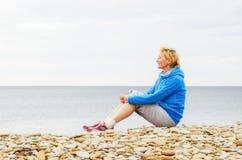 Frau, die auf dem Strand und den Blicken in den Abstand sitzt Lizenzfreie Stockfotos