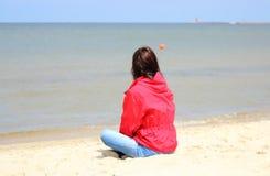 Frau, die auf dem Strand und den Blicken in Meer, Sommerzeit sitzt Lizenzfreie Stockbilder