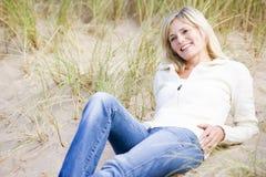Frau, die auf dem Strandlächeln liegt Stockfotografie